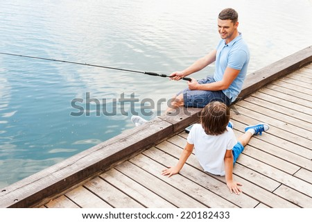 My father is the best in fishing. Top view of cheerful father and son fishing together while sitting at the riverbank - stock photo