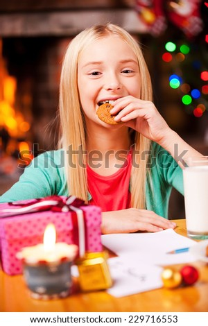My favorite Christmas cookies! Cute little girl eating a cookie and smiling while sitting at the table with Christmas Tree and fireplace in the background  - stock photo