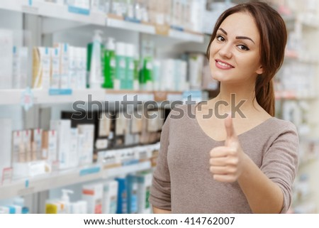 My favorite pharmacy. Cheerful female drugstore customer showing thumbs up gesture smiling happily. - stock photo