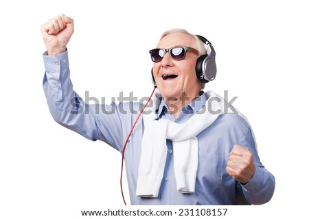 My favorite song! Cheerful senior man in headphones keeping arms raised and expressing positivity while standing against white background  - stock photo