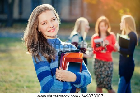My future is in my hands. Handsome young caucasian woman holding books and smiling while standing near university building and with her friends chatting in the background - stock photo