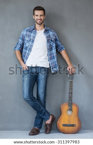 My guitar is always with me. Full lengthof young man leaning at the guitar and looking at camera while standing against grey background - stock photo