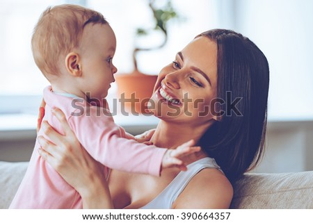 My little girl! Cheerful beautiful young woman holding baby girl in her hands and looking at her with love while sitting on the couch at home - stock photo