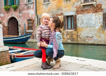 My mommy is the best, thinks this little girl, as her mother nuzzles her lovingly as she is kneeling down next to her. - stock photo