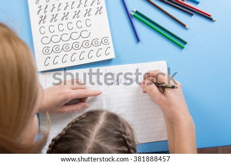 My mother helps the child to spell the letters of the alphabet, a top view - stock photo