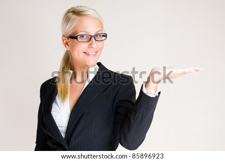 My offer, portrait of a beautiful young blond business woman holding out the palm of her hand. - stock photo