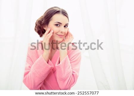 My skin is perfect. Attractive young woman in bathrobe touching her ideal skin and looking at camera with a smile in a luxurious bathroom - stock photo