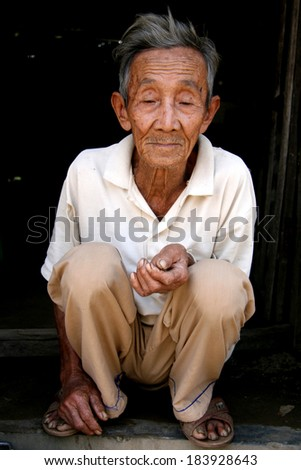 MY SON, VIETNAM - FEBRUARY 02 2007: Elderly man during Tet Holiday New Year Period at My Son Sanctuary in Vietnam. - stock photo