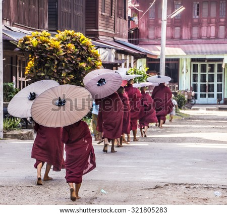 MYEIK, MYANMAR - FEBRUARY 20, 2015: Buddhist monks are walking in a row in the morning  in the streets of Myeik in the south of Myanmar. - stock photo