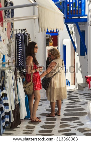 MYKONOS ISLAND, GREECE- MAY 24 2014:Street and souvenir shop in Mykonos.  Unidentified tourists walking around and shopping at shops in the narrow streets of Mykonos town, Mykonos island,  - stock photo
