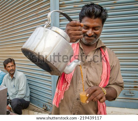 MYSORE, INDIA - FEBRUARY 8, 2013 - Men pours cup hot milk tea Indian style or chai for customers from his shop along street - stock photo
