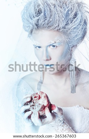 Mysterious and unusual girl with face art in the form of the Snow Queen. Girl holding a human heart in the blood. Bloodthirsty girl looking at the camera. The concept of eternal winter. - stock photo