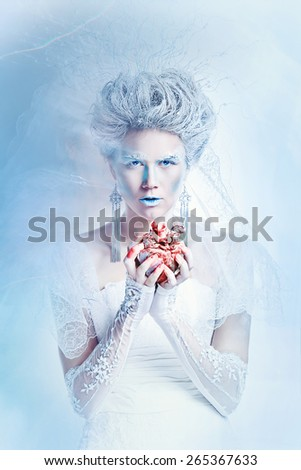 Mysterious and unusual girl with face art in the form of the Snow Queen. Girl holding a human heart in the blood. The concept of eternal winter. - stock photo
