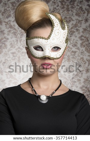 Mysterious beautiful woman in close-up carnival portrait with elegant blonde hair-style, necklace and cute decorated mask.  - stock photo