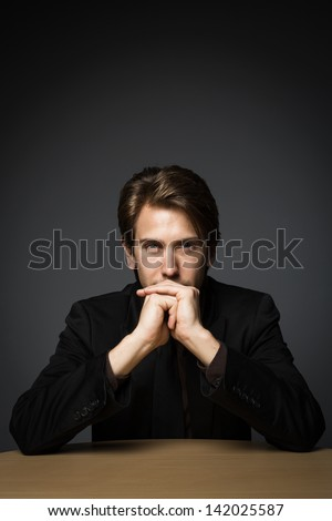 Mysterious handsome young man sitting at a table with his chin in his hand and an enigmatic expression - stock photo