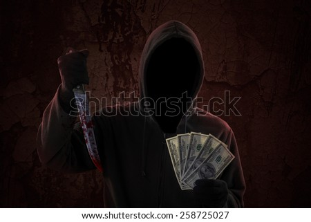Mysterious man wearing hoodie while holding bloody knife and money cash - stock photo
