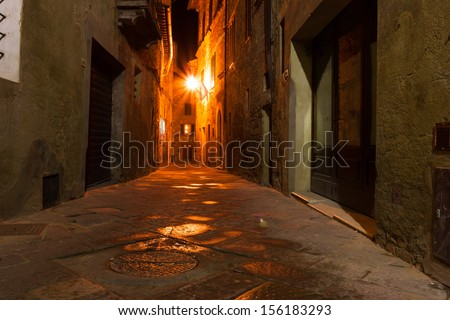 mysterious narrow alley with lanterns at night - stock photo