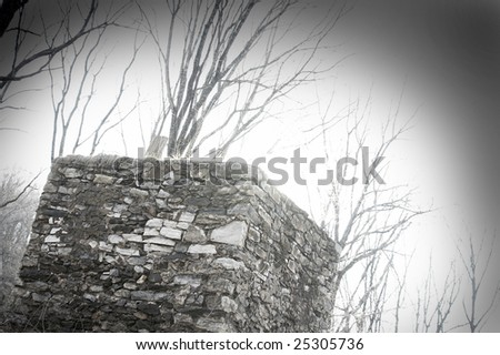 Mysterious old stone structure and barren winter trees. - stock photo
