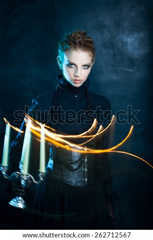 Mysterious portrait of beautiful females,  girl holds a candle  - stock photo