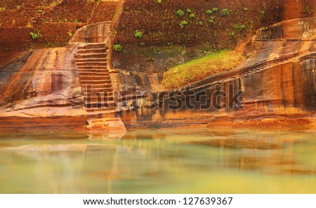 Mysterious scenic view of green pond water against the background of carved wall with scale in Sigiriya Ancient Fortress (Lion's Rock) - UNESCO World Heritage Site, Sri Lanka island, South Asia - stock photo