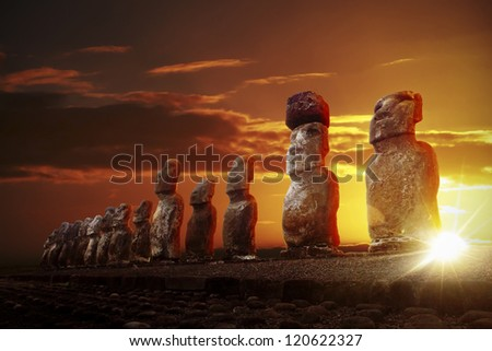 Mysterious stone statues at dramatic orange sunrise in Easter Island - stock photo