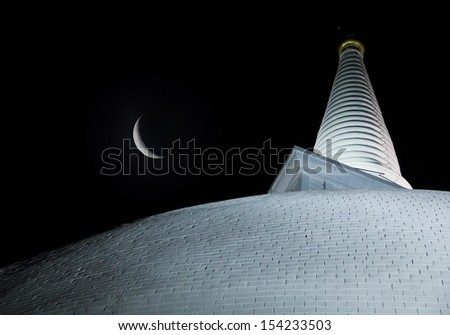 Mysterious view of white Ruwanwelisaya Chedi (Mahathupa Dagaba) - UNESCO World Heritage Site and new moon against the background of night sky in the sacred city of Anuradhapura, Sri Lanka, South Asia - stock photo