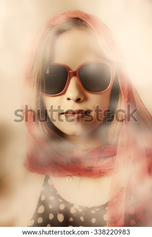 Mysterious vintage portrait on the face of a classic 50s pinup woman wearing head scarf and sunglasses in a high key enigmatic haze. Old-fashioned beauty - stock photo