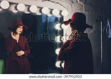 Mysterious young woman in a pink hat, old-fashioned. Stands near  mirror. Makeup. Backstage. - stock photo