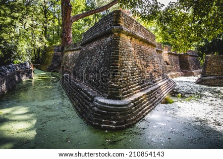 mystery, building in ruins on a green swamp with water - stock photo