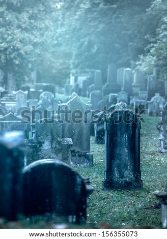 Mystery misty 19th century graveyard with a group of tombstones - stock photo