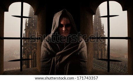 Mystery monk with the runes on the face. Sanctus Vitus church on the background. - stock photo
