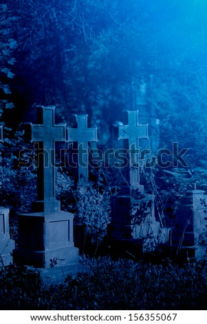 Mystery old graveyard with a group of cross tombstones - stock photo