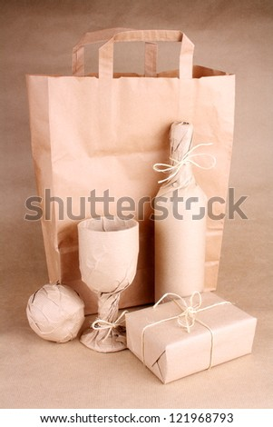 Mystery still life wrapped in brown paper on brown background - stock photo