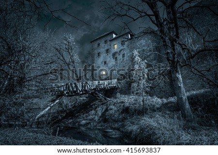 Mystic castle in the night with moat - stock photo