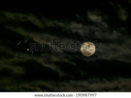 Mystic silhouette of a cat looking at the full moon - stock photo