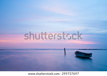 Mystical sea. Abstract natural backgrounds. Moon scene after sunset with still water and vintage boat. - stock photo
