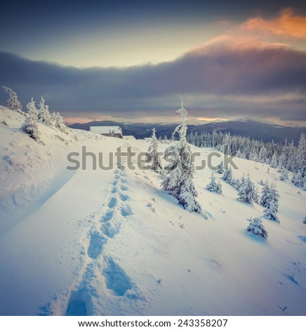 Mystical winter sunset in mountains. Old ranch after huge snowfall. Retro style. - stock photo