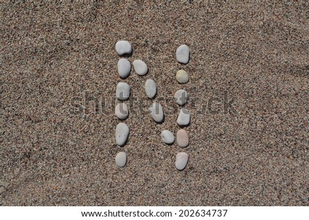 N letter made of stones on sand  - stock photo