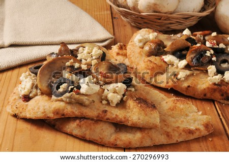 Naan bread with feta cheese, black olives, mushrooms for topping - stock photo