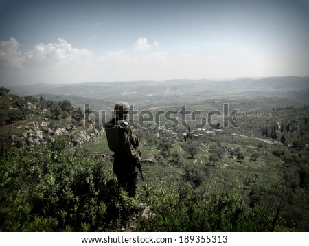 NABLUS, ISRAELI OCCUPIED TERRITORIES IN THE WEST BANK - 24, APRIL, 2007: An Israeli soldier with the Israeli Defense Forces overlooks the hills around Nablus while being on patrol. - stock photo