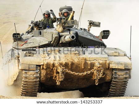 NACHAL OZ, ISR - NOV 12:Israeli soldiers drive Merkava on NOV 12 2008.It's IDF battle tank designed for rapid repair of battle damage, survivability, cost-effectiveness and off-road performance. - stock photo