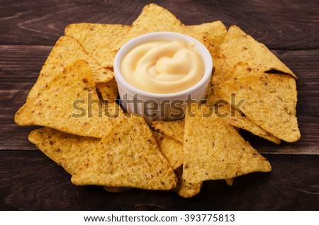 Nachos and cheese dip on table - stock photo