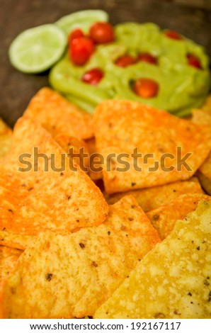 nachos and guacamole dip, avocado close up - stock photo