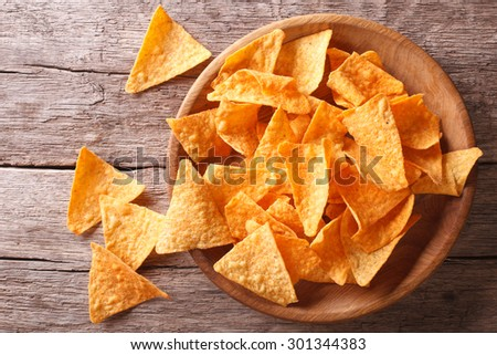 Nachos corn chips in the bowl on the table. Horizontal top view - stock photo