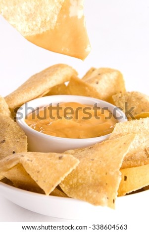 Nachos in the Bowl and Cheese Sauce in the Dipper on the Grey Background - stock photo