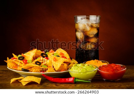 nachos plate, salsa, cheese and guacamole dip and cola drink - stock photo