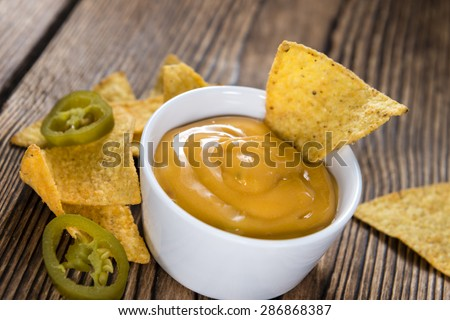 Nachos with Cheese Dip (close-up shot) on an wooden table - stock photo