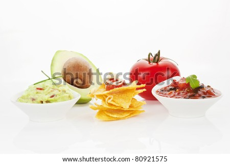 Nachos with guacamole and tomato dip and fresh avocado and tomato isolated on white background. - stock photo