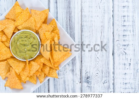 Nachos with Guacamole (close-up shot) on wooden background - stock photo
