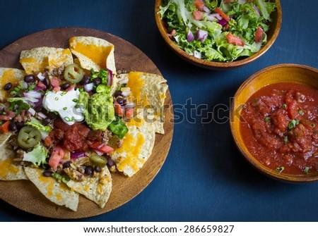 Nachos with guacamole sour cream tomato salsa and salad on moody dark blue background - stock photo